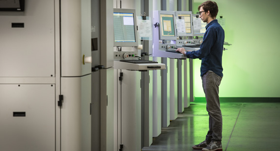 3d printing technician evaluates file on selective laser sintering machine equipment