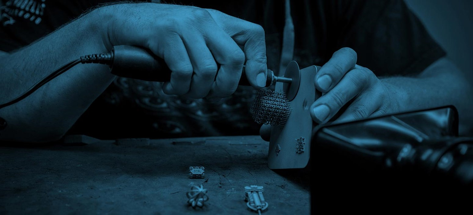 a metal 3D printing technician removes support structures from a DMLS part